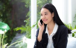 Portrait of woman sitting at sofa while talking a call at home. Business people Stock Images
