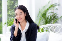 Portrait of woman sitting at sofa while talking a call at home - Business people. The portrait of woman sitting at sofa while talking a call at home - Business Royalty Free Stock Photo