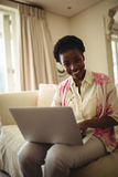 Portrait of woman sitting on sofa and using laptop in living room Royalty Free Stock Photo