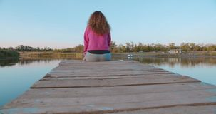 Portrait of a woman sitting on a wooden pier, looking at the lake feels free. Concept freedom, beautiful lake view. Happy people, vacation stock video footage