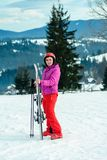 Portrait of a woman skier in red outfit against the background of Carpathian mountains stock photography