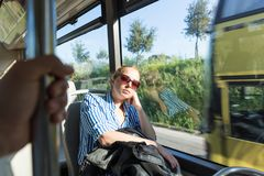 Portrait of tired woman sleeping on bus. Portrait of woman sleeping on moving bus by window. Tired passenger sleeps on long countryside bus ride home Royalty Free Stock Photography