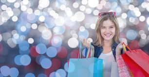 Portrait of woman smiling while holding colorful bags over bokeh Royalty Free Stock Photos