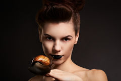 Portrait of a woman with snail. Fashion. Gothic. Woman with snail with black eyes and lips in Gothic Halloween image stock image