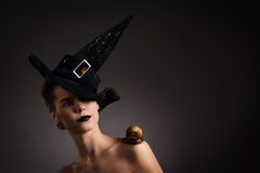 Portrait of a woman with snail in hat. Fashion. Gothic. Woman with snail on the shoulder in black hat in Gothic Halloween image Royalty Free Stock Images