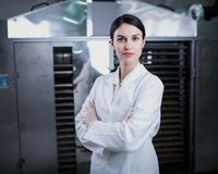 Female engineer in front of Food Dryer Dehydrator Machine. Portrait of Woman Specialist at Work in Production Facility. Female engineer technician in front of royalty free stock image