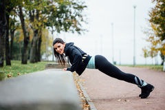 Portrait of woman in sportswear, doing fitness push-ups exercise at fall park, outdoor. stock photography