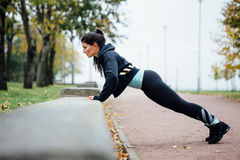 Portrait of woman in sportswear, doing fitness push-ups exercise at fall park, outdoor. Royalty Free Stock Images