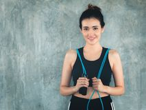 Portrait of woman in sportswear holding skipping rope at fitness club., Attractive smiling asian girl with her leisure activities royalty free stock images
