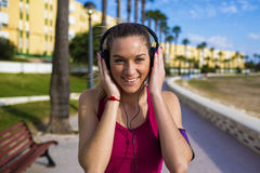Portrait of woman in sportswear smiling and listening to music Royalty Free Stock Photography