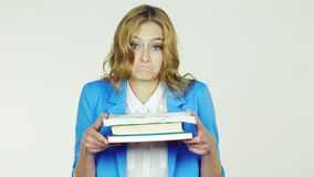 Portrait of a woman with a stack of books. A young woman holding a stack of books, embarrassment ulybaetsya.Video photographed in the studio on a white stock footage
