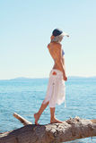 Portrait woman standing on the beach. Beautiful female wearing straw hat , looking on sea horizon, enjoying summer holiday. Stock Photos