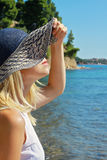 Portrait woman standing on the beach. Beautiful female wearing straw hat , looking on sea horizon, enjoying sun. Stock Image
