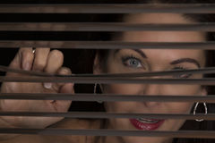 Portrait of a woman standing in darkness looking through blinds Royalty Free Stock Photos