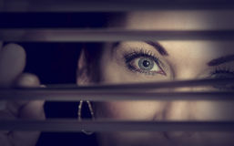 Portrait of a woman standing in darkness looking through blinds Royalty Free Stock Photography