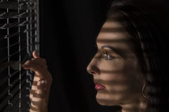 Portrait of a woman standing in darkness looking through blinds Stock Images