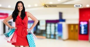 Portrait of woman standing with hand on hip and holding shopping bag Royalty Free Stock Image