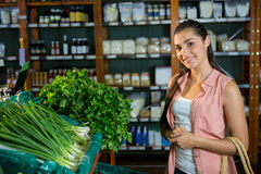 Portrait of woman standing next to scallions and herbs display in organic section Royalty Free Stock Image