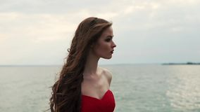 Portrait of woman, standing on a pier near the sea and looking in the distance. Portrait of a romantic and young woman who stands on a pier near the sea, she stock footage