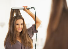 Portrait of woman straightening hair with straightener Stock Image