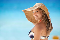 Portrait of woman with straw hat at beach smiling. Portrait of young beautiful girl at tropical beach in Cuba for vacations, looking at camera and smiling. Copy Stock Image