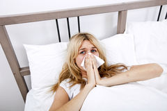 Portrait of woman suffering from cold in bed Stock Photos