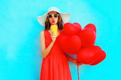 Portrait woman in summer hat drinks juice from cup with red an air balloons. On blue background Stock Photography