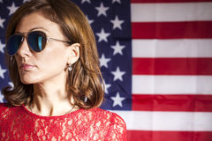 Portrait of  woman with sunglasses against american flag Royalty Free Stock Images