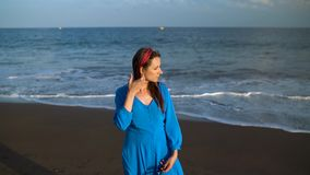 Portrait of a woman in a beautiful blue dress on a black volcanic beach stock footage