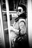Portrait of woman in sunglasses standing in payphone cabin Stock Photo