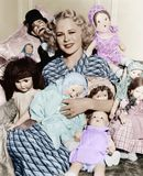 Portrait of a woman surrounded by dolls and smiling Royalty Free Stock Photos