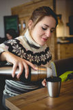 Portrait of woman in sweater pouring coffee from thermos in cup Royalty Free Stock Image