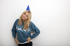 Portrait of woman in sweater wearing party hat against white background Stock Images