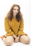 Portrait of a woman in sweater on white background. The girl in the orange sweater and socks Stock Photos