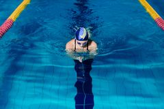 Woman swimming with swimming hat in swimming pool stock photography