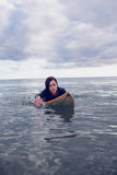 Portrait of a woman swimming over surfboard in water Stock Photography