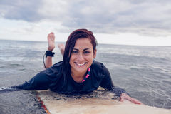 Portrait of a woman swimming over surfboard in water Royalty Free Stock Photos