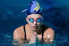 Woman swimming with swimming hat in swimming pool royalty free stock photos