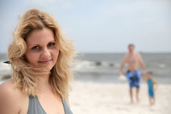 Portrait woman on on t beach and family behind her Royalty Free Stock Images