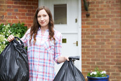 Portrait Of Woman Taking Out Garbage In Bags Royalty Free Stock Image