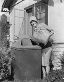 Portrait of woman taking out trash Royalty Free Stock Photography