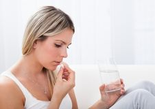 Portrait of woman taking pills Royalty Free Stock Images