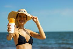 Portrait of woman taking skincare with sunscreen lotion at beach stock image