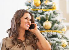Portrait of woman talking cell phone near christmas tree Royalty Free Stock Image