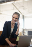 Portrait of woman talking on phone while using laptop in office Stock Images