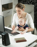 Portrait of woman teaching her baby son how to use computer Royalty Free Stock Photo