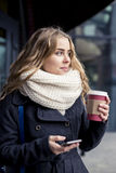 Portrait of woman texting on mobilephone. Smiling girl holding a smartphone and writing. Happy young woman standing at coffee bar Royalty Free Stock Images