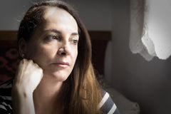 Portrait of a woman thinking. Portrait of a woman looking to a window and with a hand on her neck thinking with doubts, uncertain future Royalty Free Stock Photo