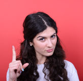 Portrait of woman threatening with finger gesture against red ba Stock Photo