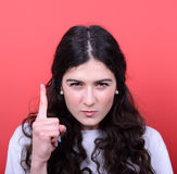 Portrait of woman threatening with finger gesture against red ba Royalty Free Stock Photos